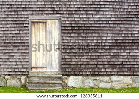 rustic door on shake sided house with stone foundation - stock photo