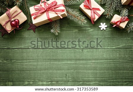 Rustic festive Christmas border with gift-wrapped presents tied with colorful red ribbon amongst fresh pine foliage across the top of the frame over green wood with copyspace - stock photo
