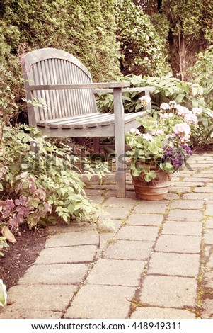 Rustic garden bench and pink geraniums in vintage.  - stock photo