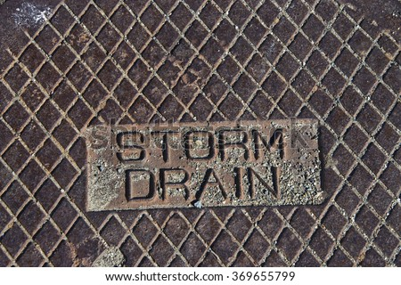 Rustic grunge storm drain manhole cover close up on storm drain carved letters - stock photo