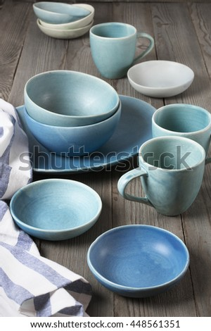 Rustic handmade blue ceramic dishware set and towel on wooden table.