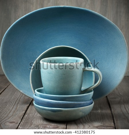 Rustic handmade blue ceramic dishware set on wooden table.