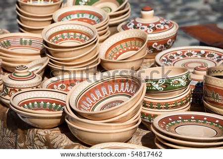 Rustic handmade ceramic and clay brown pots decorated by traditional ornament and pattern at the handicraft market - stock photo