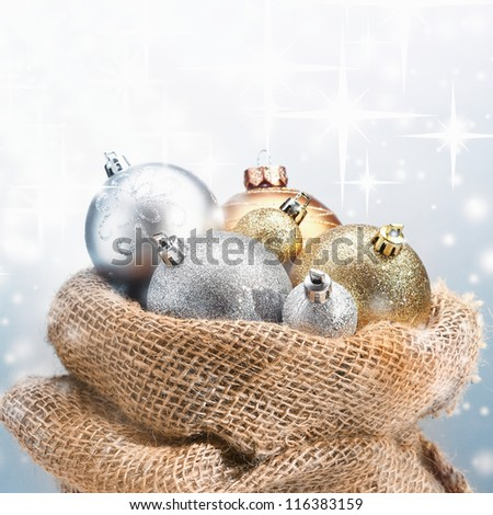 Rustic hessian sack full of Christmas decorations with decorative gold and silver baubles peeking out under sparkling falling snow with copyspace - stock photo