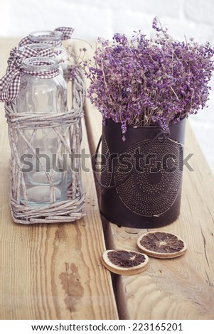 Rustic home decor, provence style. Lavender bouquet of dried field flowers and glass spice jars on wooden bench. - stock photo