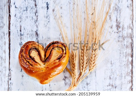 Rustic home-made heart shape cinnamon roll on white painted board or table - stock photo