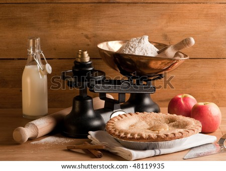 Rustic homemade apple pie with weighing scales and ingredients - stock photo