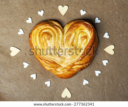 Rustic homemade heart shape bun on textured background - stock photo