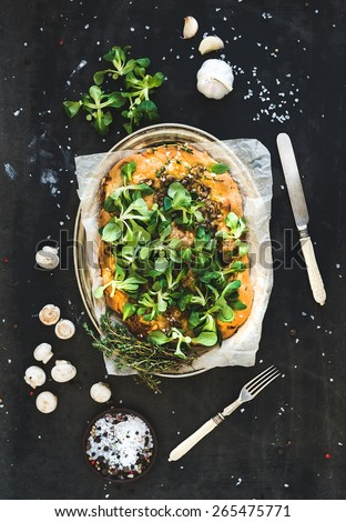 Rustic homemade pizza with fresh lamb's lettuce, mushrooms and garlic over dark grunge background, top view - stock photo