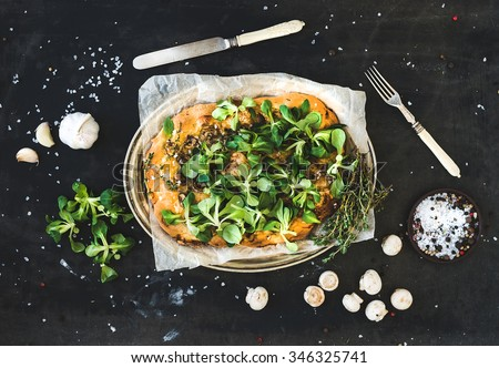 Rustic homemade pizza with fresh lamb's lettuce, mushrooms and garlic over dark grunge background, top view. Horizontal - stock photo