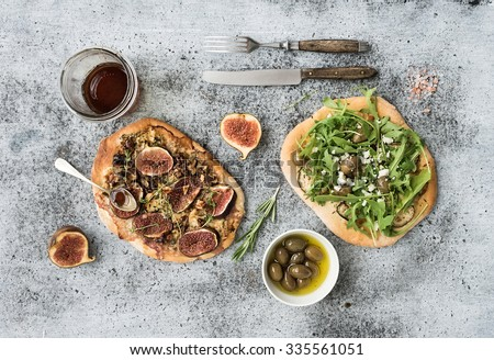 Rustic homemade pizzas with eggpant, cheese, olives, arugula, prosciutto and figs over grunge backdrop. Top view - stock photo