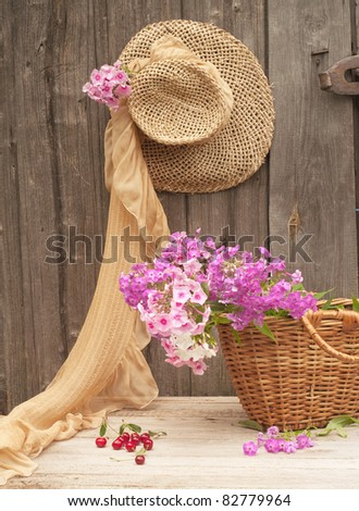 Rustic image of a gardener's straw hat and basket - stock photo