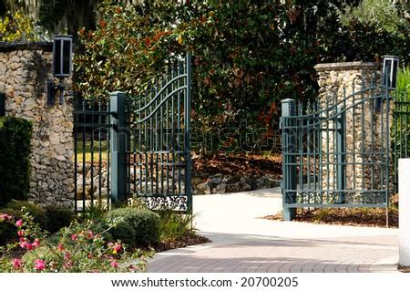 garden pillars. Rustic Iron Gates With Beautiful Stone Pillars In A Plush Garden Setting.