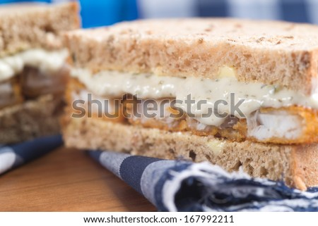 Rustic kitchen setting for fresh fish finger sandwich on wholegrain - stock photo