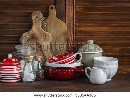 Rustic kitchen still life. Olive cutting board,  jar of flour,  bowls, pan, enamelled  jar,  gravy boat. On a dark brown wooden table. Vintage and rustic style - stock photo