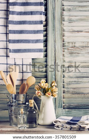 Rustic kitchen still life: white jug with roses bunch, galvanized buckets with wooden spoons, glass bottles and linen towels against vintage wooden shutters. - stock photo