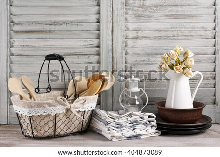 Rustic kitchen still life: wire basket with wooden spoons, jug with roses bunch, ceramic dishware, towels stack and lantern against vintage wooden shutters.