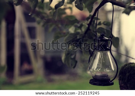 Rustic lamp hanging on tree in the garden - stock photo
