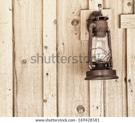 Rustic Lantern on Wood Panel Wall with room or space for text, copy, words.  Square with grunge, sepia treatment - stock photo