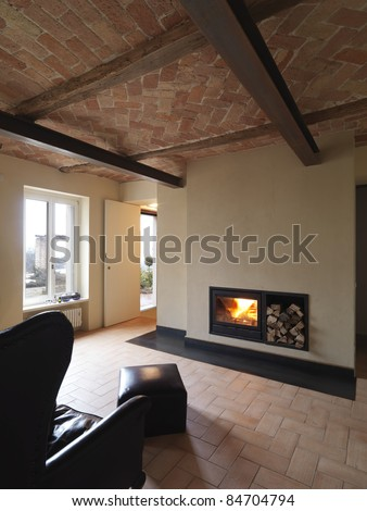rustic living room with armchair and fireplace - stock photo