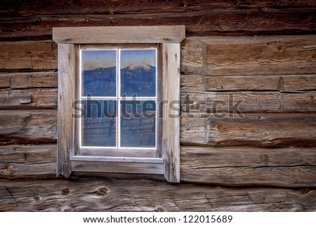 Rustic Log cabin and window with a reflection of a mountain range