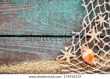 Rustic marine background with copyspace on weathered turquoise blue wooden boards decorated with diamond mesh fish net, starfish and a seashell on a bed of beach sand, mementos from a summer vacation - stock photo