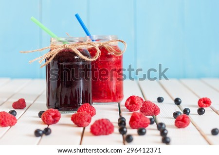 Rustic Mason Jars with raspberry jam and bog bilberry marmalade with fresh berries on white wooden background - stock photo