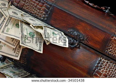Rustic metal treasure chest overflowing with cash.  Macro with shallow dof. - stock photo