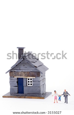 Rustic miniature house with a young couple and a child over white background. Shallow depth of field.