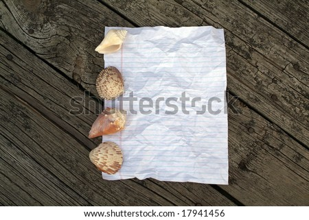 Rustic Notebook paper background  with shells and wooden pattern behind - stock photo