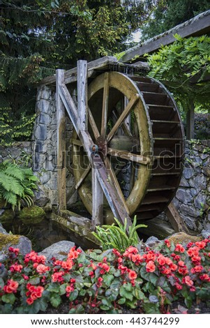 Rustic old milling water wheel in garden setting - stock photo