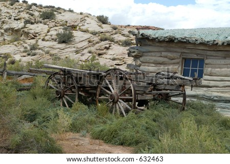 rustic old wagon by house - stock photo