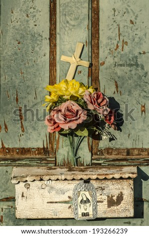 Rustic old weathered and worn doorway with charming display of flowers and cross - stock photo