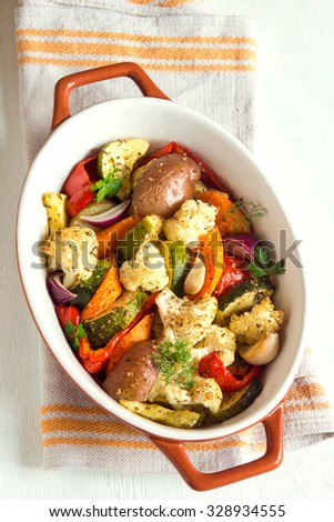 Rustic oven baked vegetables with spices and herbs in baking dish close up, vegetarian organic autumn meal - stock photo