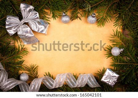 Rustic paper with silver Christmas decorations and juniper leaves around