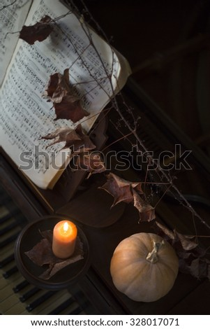 Rustic piano decorated with pumpkin, grape vine and a candle  - stock photo