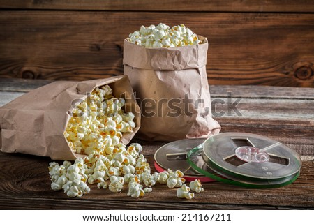 Rustic popcorn and reel tapes - stock photo