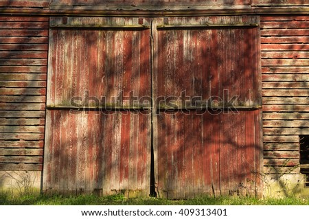 Rustic Red Barn Doors With Afternoon Light Casting Tree Shadows