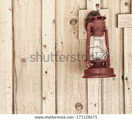 Rustic Red Lantern on Wood Panel Wall with room or space for text, copy, words. Square with grunge, sepia treatment - stock photo