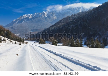 rustic road in winter, Piatra Craiului Mountains Romania