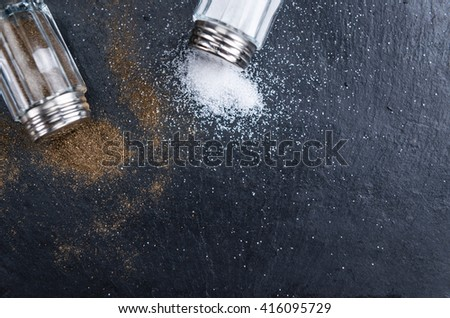 Rustic Salt and Pepper Shaker (close-up shot) on a slate slab (selective focus) - stock photo