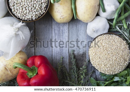 Rustic scene of fresh vegetables, lentils and bulgar wheat with copy space.