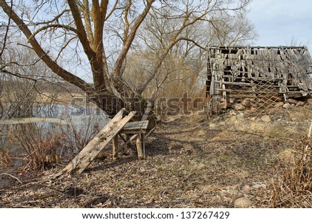 Rustic scenery with old wooden table under tree and ramshackle barn behind - stock photo