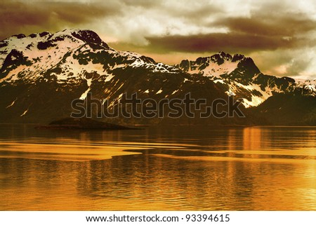 Rustic sepia view of an Alpine mountains chain next to the sea. - stock photo