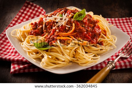 Rustic serving of traditional Italian spaghetti Bolognese topped with fresh basil and grated cheese on a modern square white plate and checkered re and white napkin - stock photo