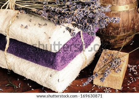 Rustic setting with natural soap, towels and lavender - stock photo