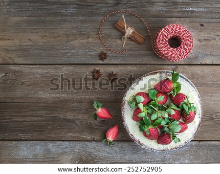 Rustic spicy ginger cake with cream-cheese filling and fresh strawberries over a rough wood background with a copy space. Top view - stock photo