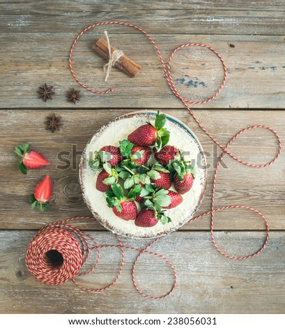 Rustic spicy ginger cake with cream-cheese filling and fresh strawberries with a rough wood background. Top view - stock photo