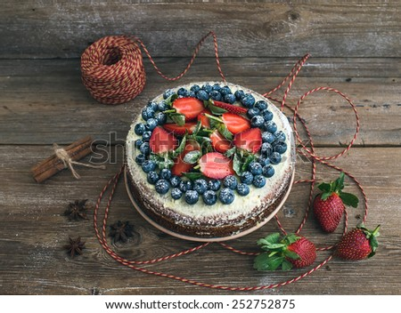 Rustic spicy ginger cake with cream-cheese filling, fresh strawberries and blueberries over a rough wood background with a decorative rope  - stock photo