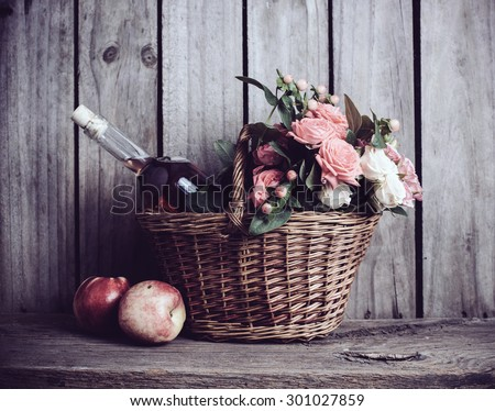 Rustic still life, fresh natural pink roses and a bottle of rose wine with nectarines in a wicker basket on an old wooden barn board background. Flowers and fruits for vintage wedding with copy space. - stock photo